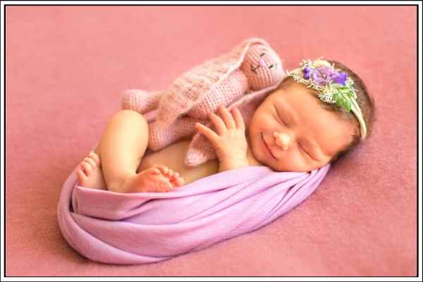 swaddled newborn baby with a smile on her face, and a pink bunny teddy right next to her.
