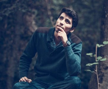 man sitting in the woods wondering something with a hand in front of his mouth