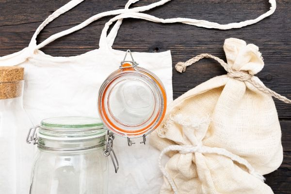 Natural reusable storage options for food, a glass, a cotton bag, and a glass water pitcher.