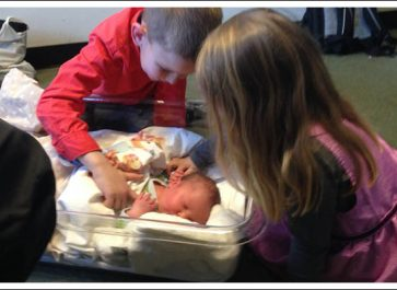 Siblings looking at a newborn baby.