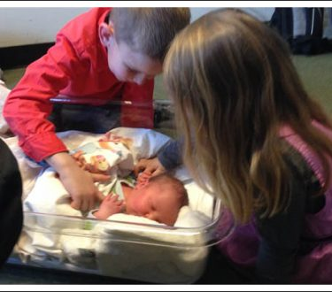 Siblings looking at a newborn baby.
