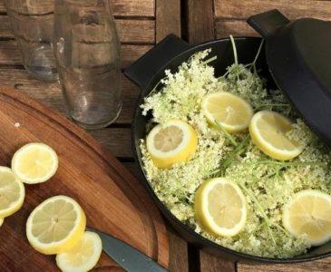Elder flowers and lemons in a cast iron pot, ready for making elderflower cordial