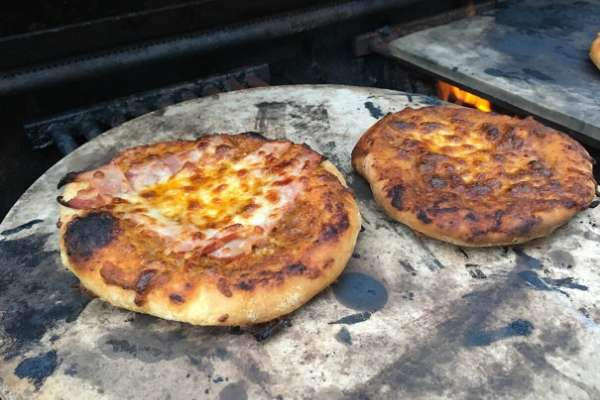 two small pizzas on a pizza stone on an outdoors grill