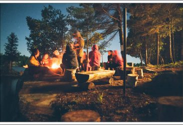 People seated around the campfire in a dark camping environment