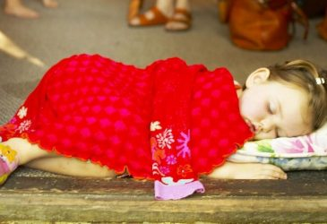 Toddler sleeping on a small matress with a blanket