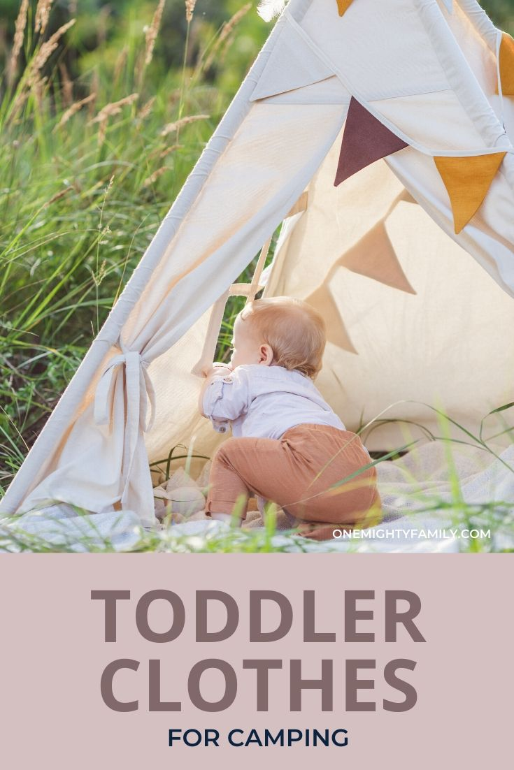 Toddler looking out from a tepee outdoors