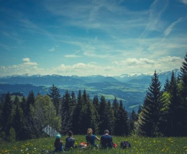 Family sitting in the grass on a mountain top