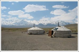 two yurts in the vast space of rural Mongolia with a big blue skye and lots of clouds