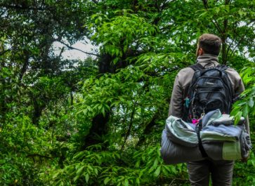 man hiking in the woods with a backpack with a rolled up sleeping bag