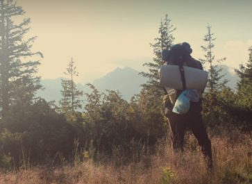 man hiking with sleeping pad and backpack in mountaines landscape