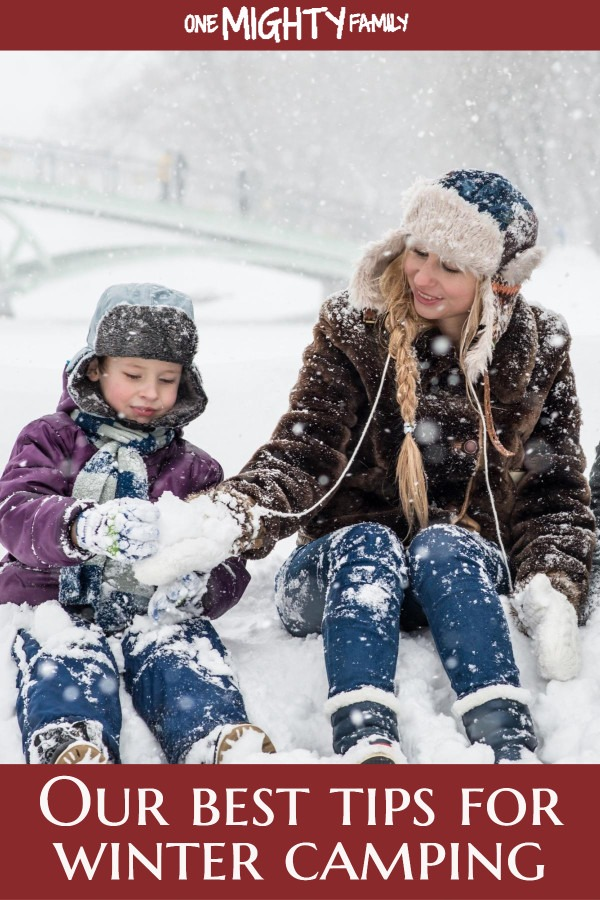 A grown up and a child in winterclothes with snow all around them, happy together outside